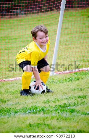 Young boy or kid playing soccer goalie - stock photo