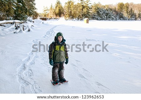 young boy out snow shoeing across a frozen lake - stock photo