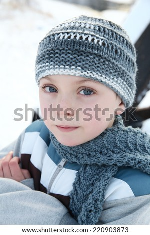 Young boy outside in the snow wearing blue - stock photo
