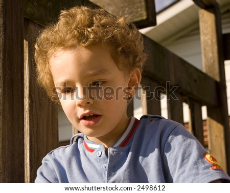 Young boy outside with surprise look on face - stock photo