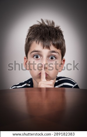 Young boy peeking over the table and holding a index finger on his lips - stock photo