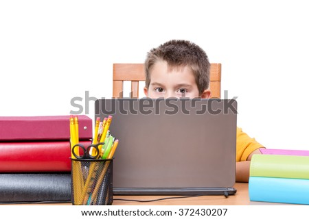 Young Boy Peeking Over Top of Laptop Computer Screen While Studying at Desk with Pencil Holder and Supplies and Surrounded by Colorful Books and Binders, in Room with White Background and Copy Space - stock photo