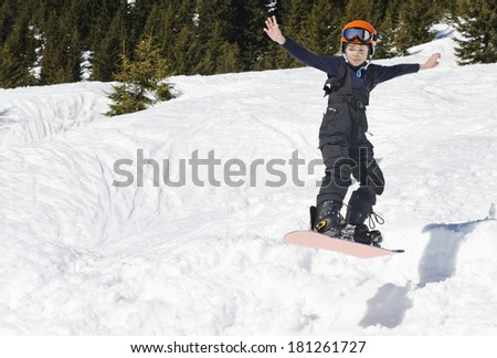 Young boy performing a jump on a snowboard - stock photo