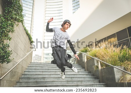 young boy performing parkour movement in the city center - stock photo