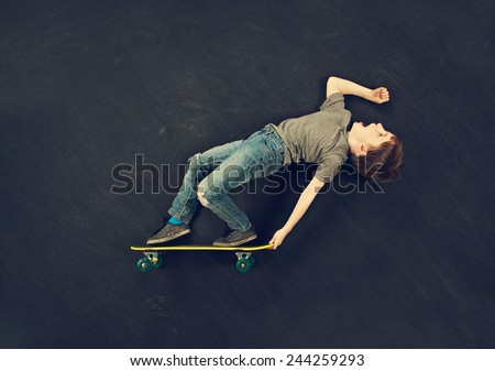 Young boy performing skateboard trick - stock photo