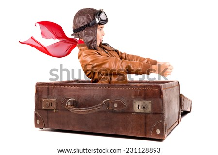 Young boy pilot flying an old suitcase isolated in white - stock photo