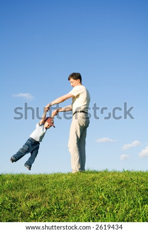 Young boy played with father. Green grass. Blue sky. 7 - stock photo