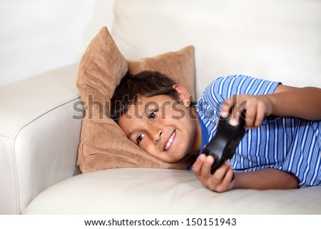 Young boy playing computer game while relaxing on the sofa - stock photo