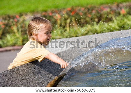 young boy playing in a public fountain - stock photo