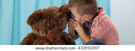Young boy playing in doctor with bear - stock photo