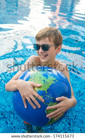 Young Boy Playing in Pool on Vacation Floating on Earth Shaped Ball - stock photo