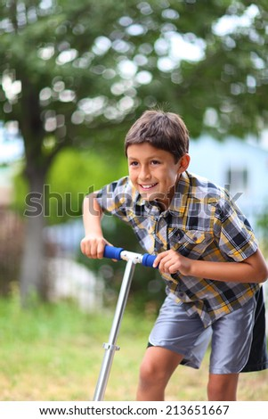 Young boy playing on a scooter - stock photo