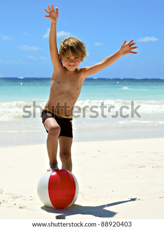 young boy playing on the tropical beach with a ball - stock photo