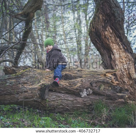 Young boy playing outdoor at spring day, sitting on fallen old tree. Happy caucasian boy. - stock photo