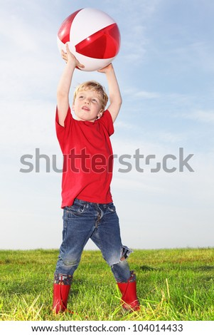 Young boy playing outdoors with a ball - stock photo