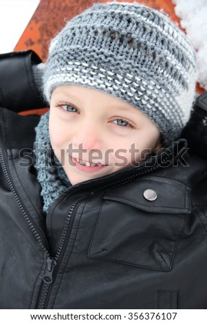 Young boy playing outside on a snowy day - stock photo
