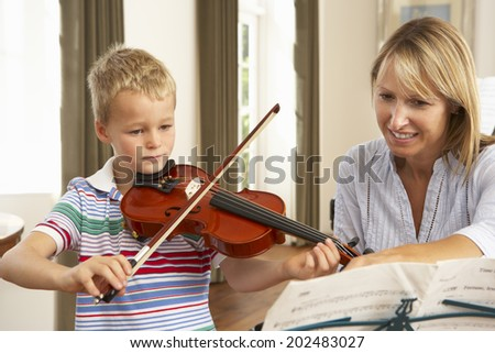Young boy playing violin in music lesson - stock photo