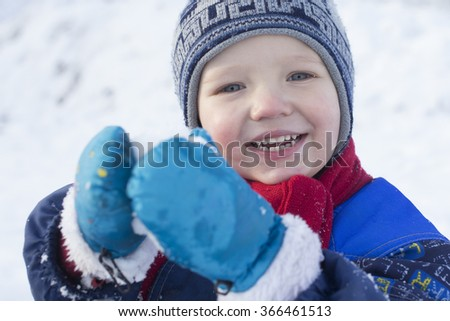 Young boy playing with a snowball - stock photo
