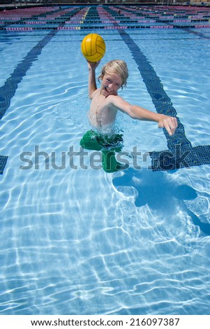 Young boy playing with ball in swimming pool - stock photo