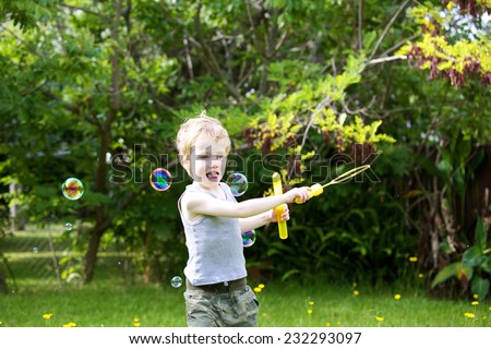 Young boy playing with bubbles in the garden. - stock photo