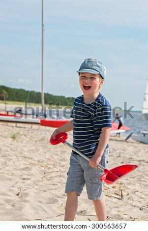 Young boy playing with sand and on shovel beach - stock photo