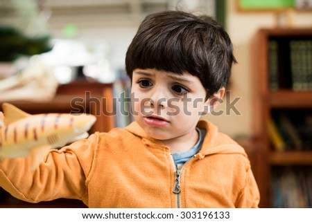 Young boy playing with shark toy - stock photo