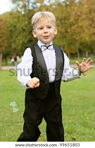 young boy playing with soap bubbles - stock photo