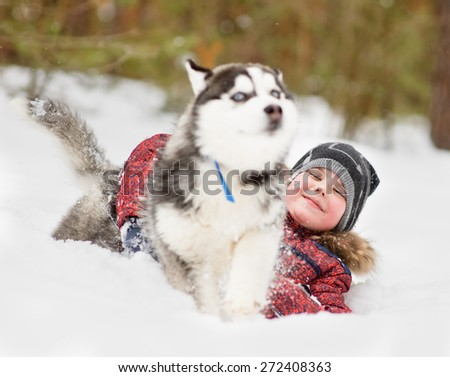 young boy playing with the dog in the snow - stock photo
