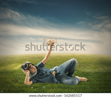Young boy playing with toy airplane in a green field - stock photo