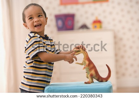 Young boy playing with toy dinosaur - stock photo
