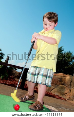 Young boy plays mini golf at putt putt course. - stock photo