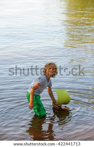 Young boy plays with his homemade sailing boat in calm lake water. It is summertime. He looks at the camera - stock photo
