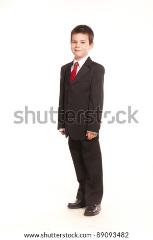 Young boy posing in studio in a black suit and a red tie, business code, on white - stock photo