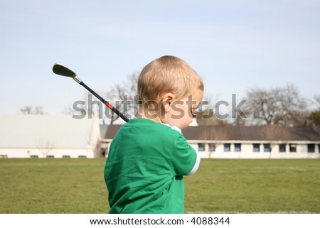 Young boy practicing golf on the driving range - stock photo