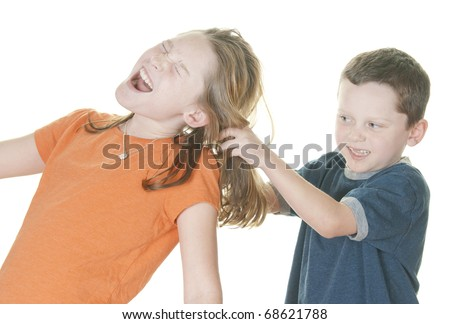 young boy pulling girl's hair - stock photo