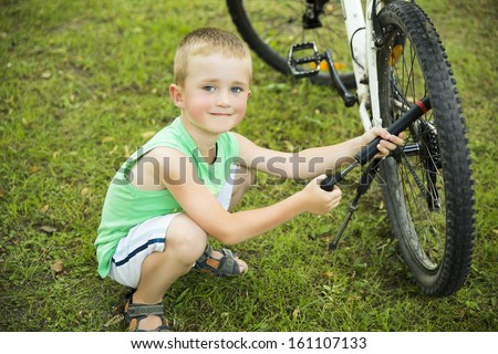 Young boy pumping the? bicycle tube on meadow - stock photo