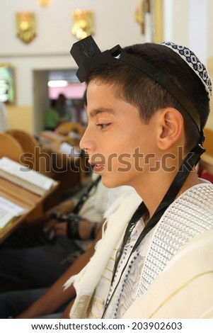 Young boy put Tefilin in a Synagogue - stock photo