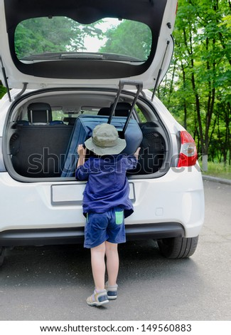 Young boy puts the suitcase in the trunk of a car - stock photo