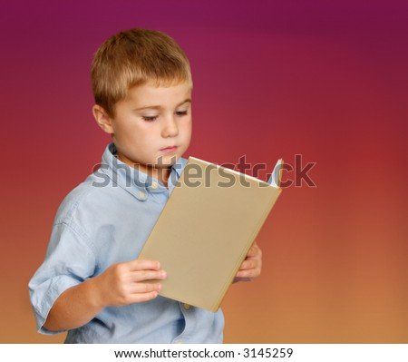 Young boy reading a book against isolated background - stock photo
