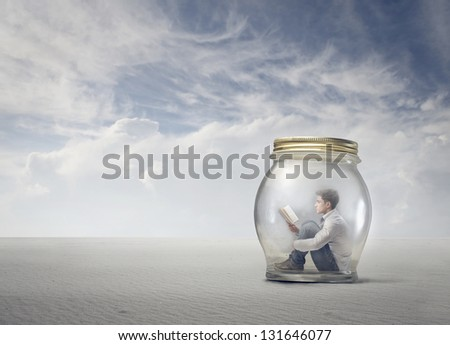 young boy reads book sitting in a jar in the desert - stock photo
