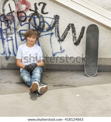young boy relaxes with his skate board at the skate park - stock photo