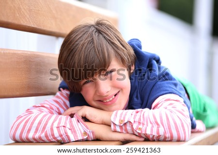 Young boy relaxing on bench in park - stock photo