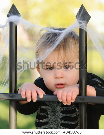 Young boy resting against webbed fence - stock photo