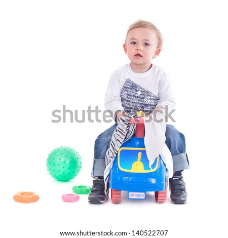 Young boy riding a toy car - stock photo