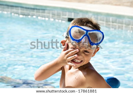 Young boy rubbing his eyes wearing goggles after a swim in the pool. - stock photo