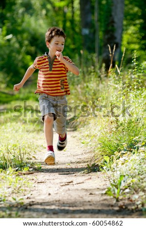 Young boy running in nature - stock photo