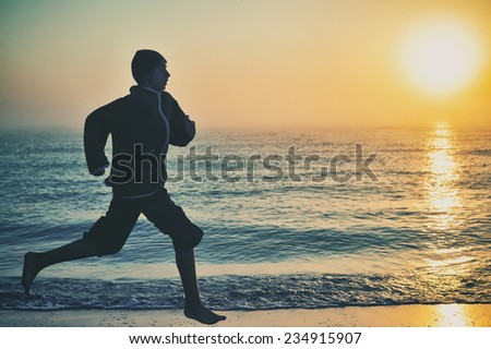 Young boy running on beach at sunrise - stock photo
