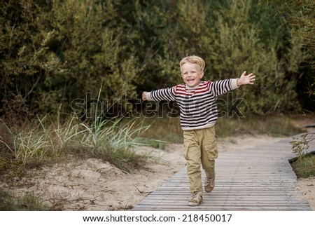 Young boy running with open arms. Oudoor portrait - stock photo