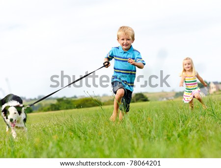 Young boy runs in a green field with his new pet with his sister following behind - stock photo