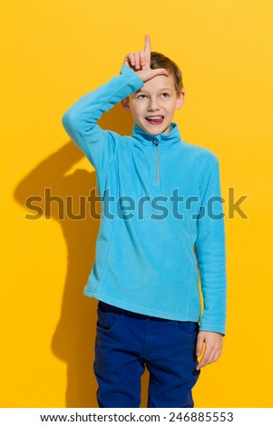 Young boy showing L hand sign for loser. Three quarter length length studio shot on yellow background. - stock photo